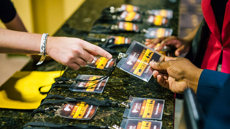 close up of event attendee hands grabbing their name lanyards at Kalahari Resorts and Conventions