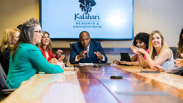 Group of 10 around a table in a smaller meeting space at Kalahari Resorts and Conventions