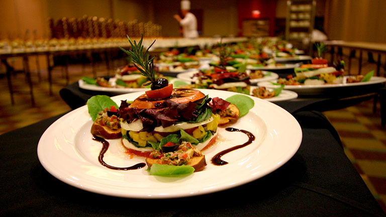 Close up of a plated stacked caprese salad with bruschetta and balsamic swirl on the side