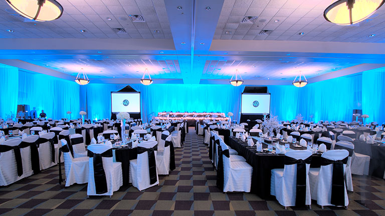 Wisconsin Dells Kalahari Ballroom with blue back lighting, two presentation screens and formal place setting