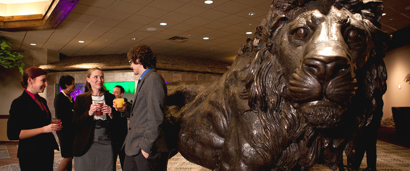 A group of event attendees talking near a large lion sculpture in the hallway
