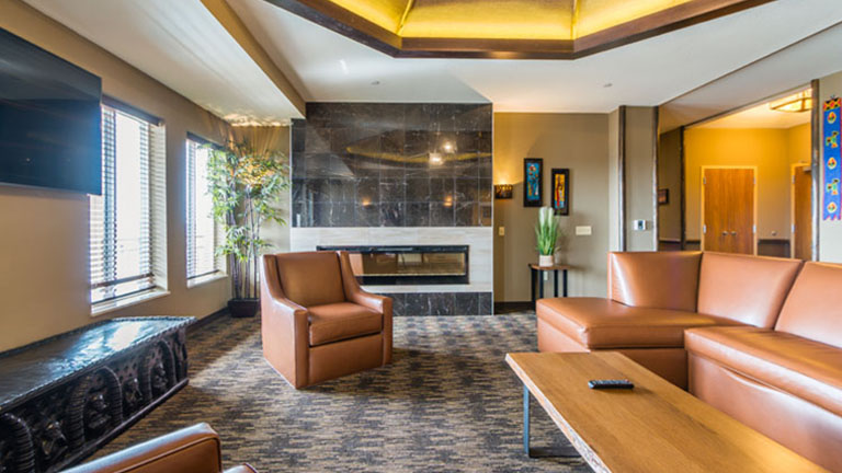 Living room area with tan leather couches in the penthouse suite at Kalahari Resorts & Conventions in Pocono Mountains, Pennsylvania